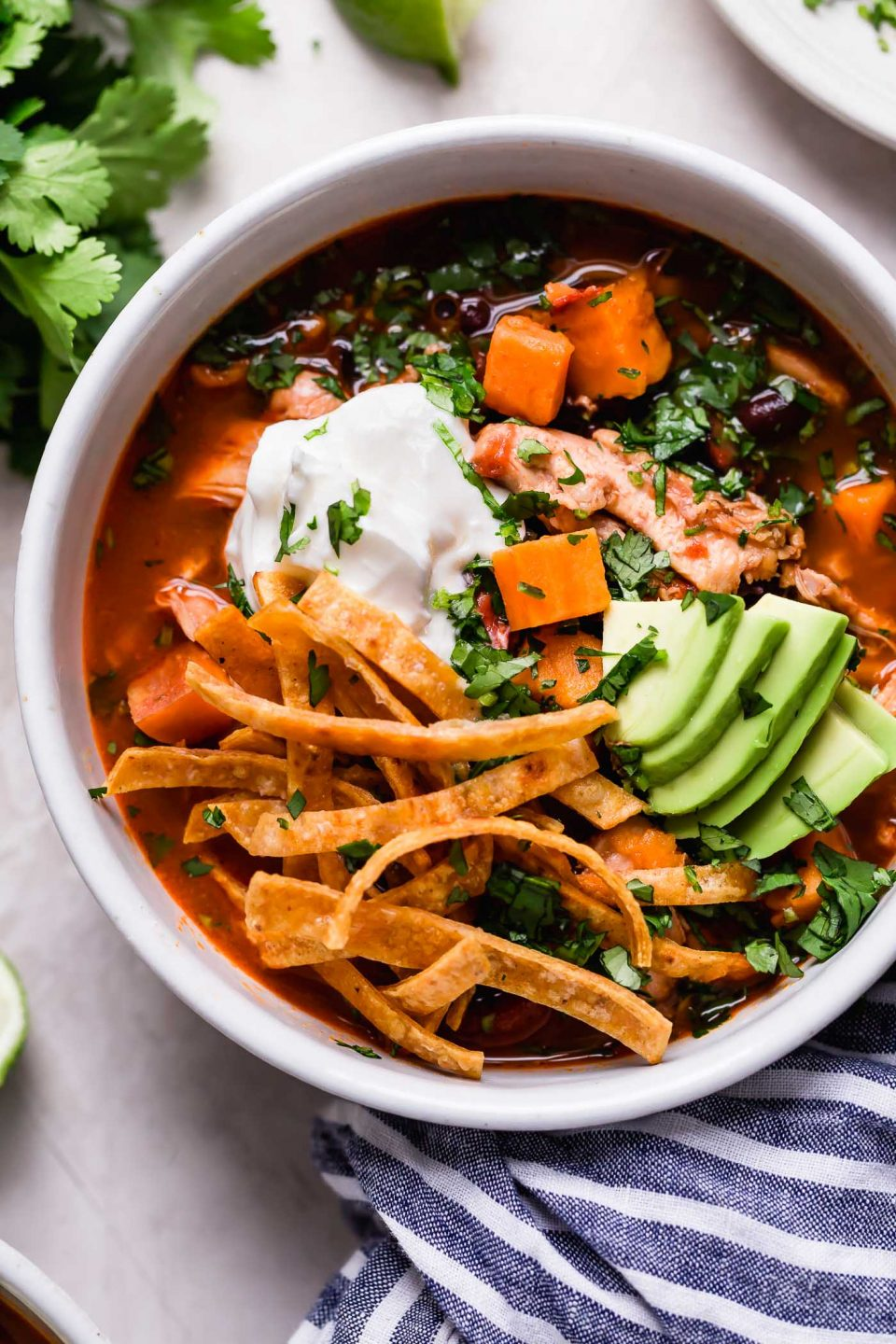 An overhead shot of a white bowl filled with Tortilla Soup topped with sour cream, fried tortilla strips, sliced avocado, & chopped cilantro. The bowl sits on top of a white background with a bunch of cilantro and a blue and white striped linen napkin.