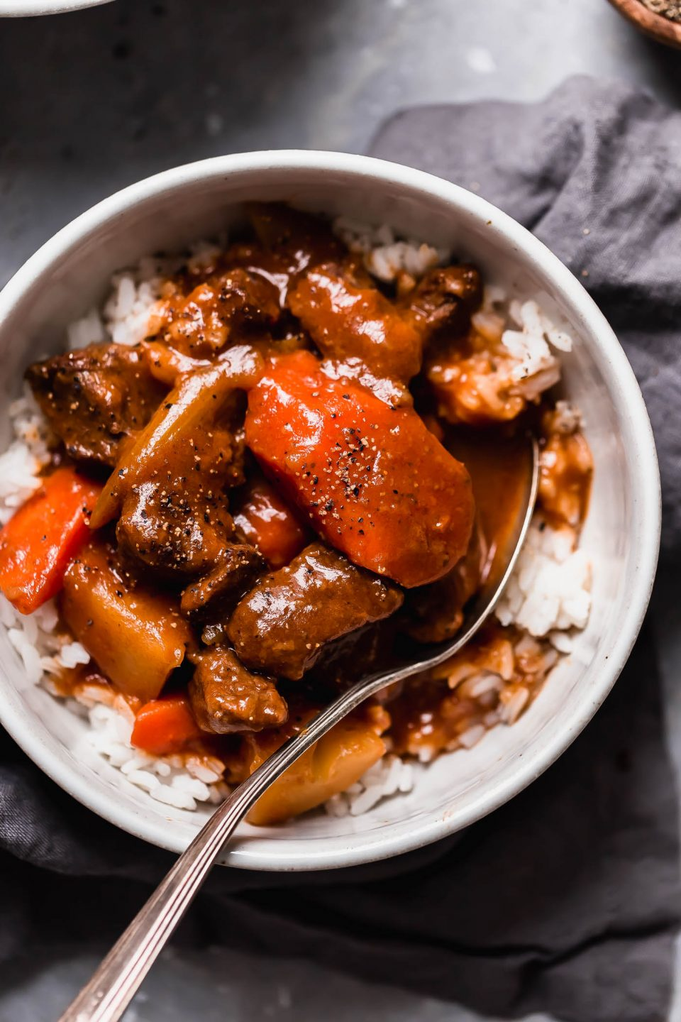 Hawaiian Beef Stew served in a white bowl over sticky rice. The bowl is on a grey-ish blue background, with a grey linen.