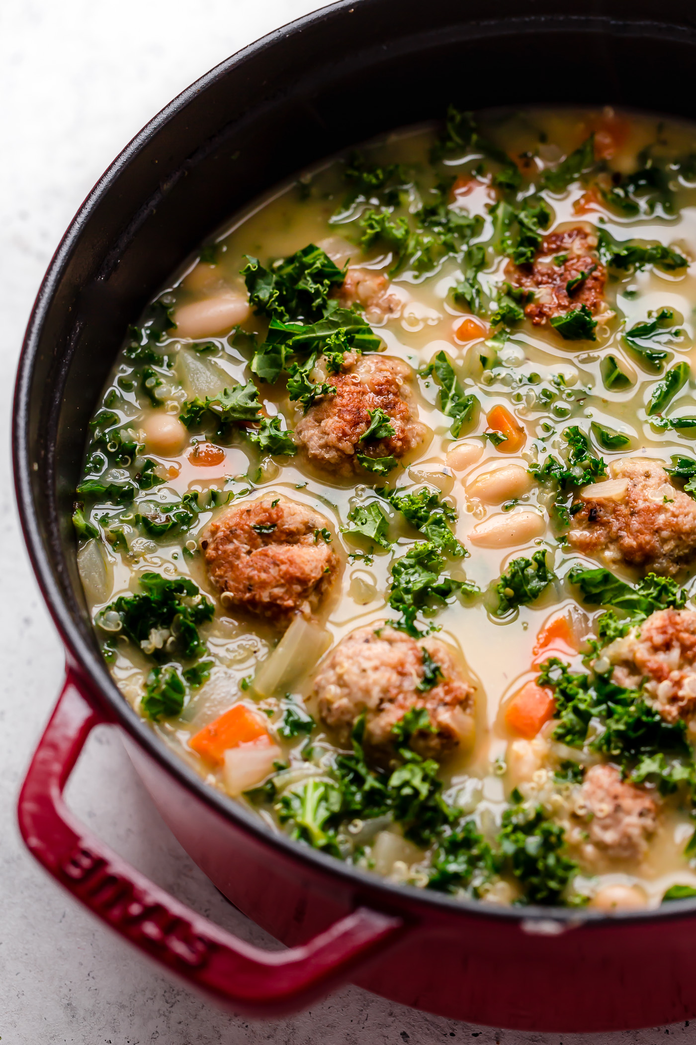 a healthy italian wedding soup recipe, made with tender chicken meatballs, quinoa, kale & cannellini beans. this lightened-up italian wedding soup gets an extra punch of flavor from lemon juice & lots of pesto, making it a cozy & comforting soup & fresh easy weeknight dinner all at once! #playswellwithbutter #italianweddingsoup #italianweddingsouprecipe #easyitalianweddingsoup #chickenmeatballsoup #chickenmeatballs #souprecipes #comfortfood #comfortfooddinners #soup #italianrecipes #italiansoup