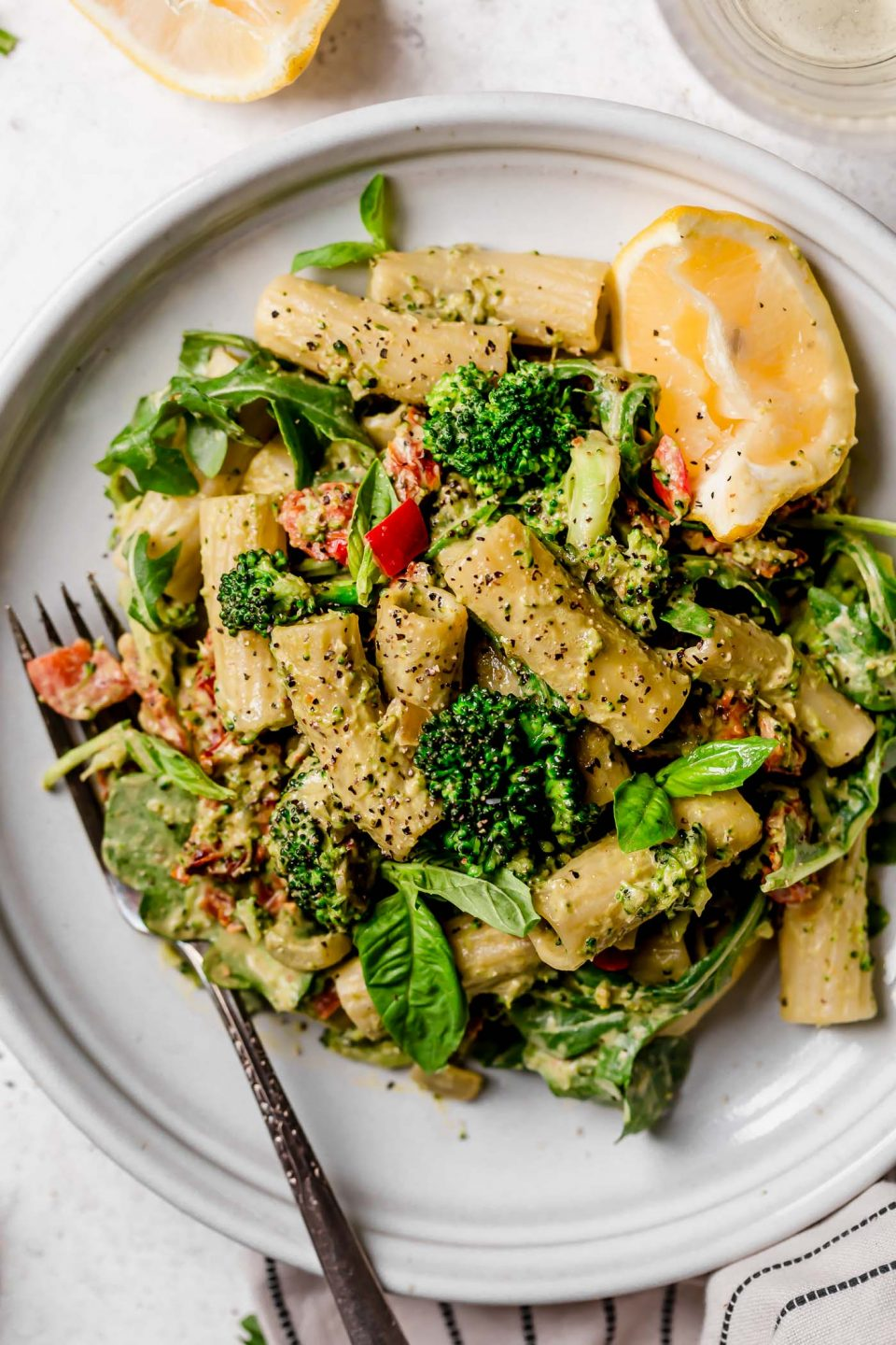 Creamy vegan pasta, tossed with broccoli, bell peppers, & arugula, served on a small white plate. The plate is placed on a white surface next to a black & white striped linen & a glass of white wine.