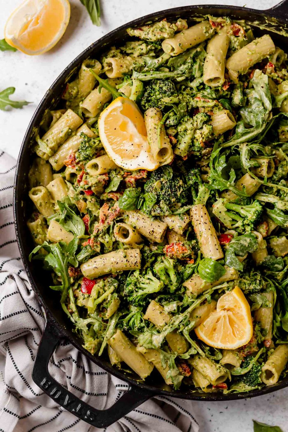 Creamy vegan pasta, tossed with broccoli, bell peppers, & arugula, served in a Staub skillet. The skillet is placed on a white surface next to a black & white striped linen.
