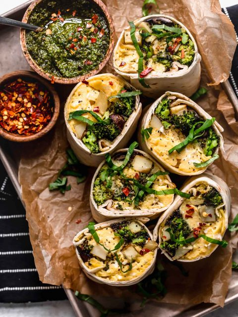 an easy vegetarian breakfast burritos recipe, filled with soft-scrambled eggs, cheese, roasted broccoli, mushrooms & potatoes, & a drizzle of fresh pesto for freshness. pesto roasted veggie vegetarian breakfast burritos are the perfect healthy make-ahead breakfast for weekdays! (meal prep & freezer-friendly) #breakfastburritos #vegetarianbreakfastburritos #easybreakfastburritos #makeaheadbreakfast #freezerbreakfastburritos #breakfastrecipes #makeaheadbreakfastrecipes #easybreakfastrecipes