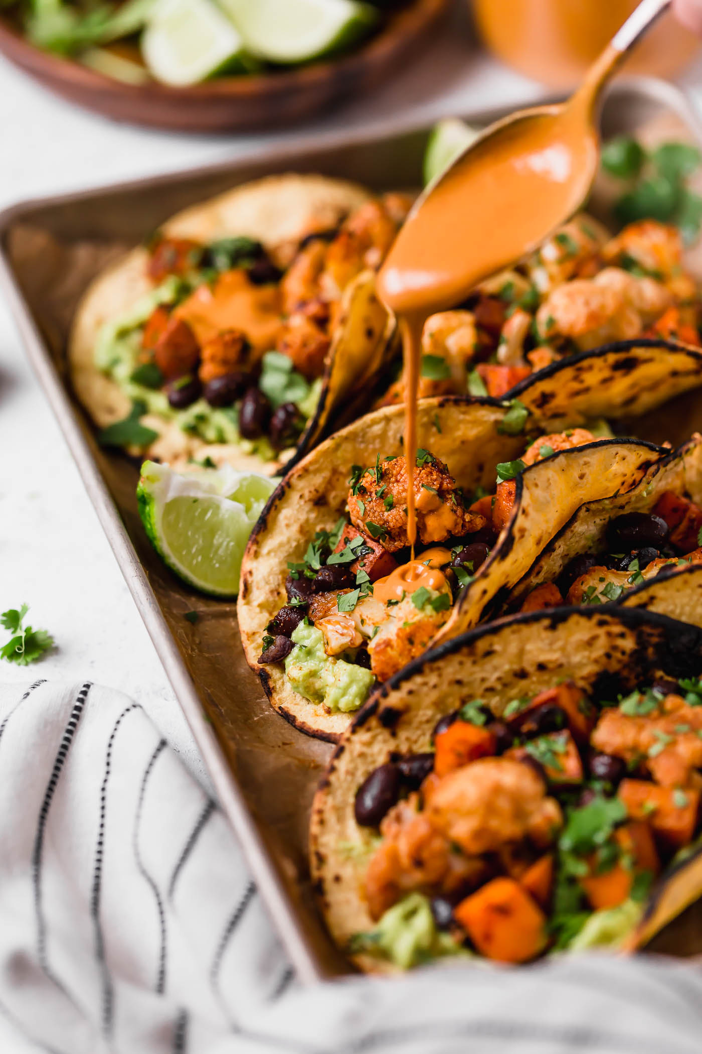 an easy vegetarian tacos recipe filled with easy roasted cauliflower, roasted sweet potatoes, black beans, topped with vegan chipotle lime cashew crema. these roasted sweet potato + cauliflower tacos are totally weeknight-friendly, made in 40 minutes or less, making this the perfect vegetarian taco recipe for taco tuesday! #tacos #cauliflowertacos #sweetpotatotacos #blackbeantacos #vegetariantacos #vegantacos #healthytacosrecipe #easytacosrecipe #easyvegetarianrecipe #easyveganrecipe #dairyfree