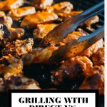 Grill tongs picking up a grilled chicken wing on a grill with graphic text overlay for Pinterest.