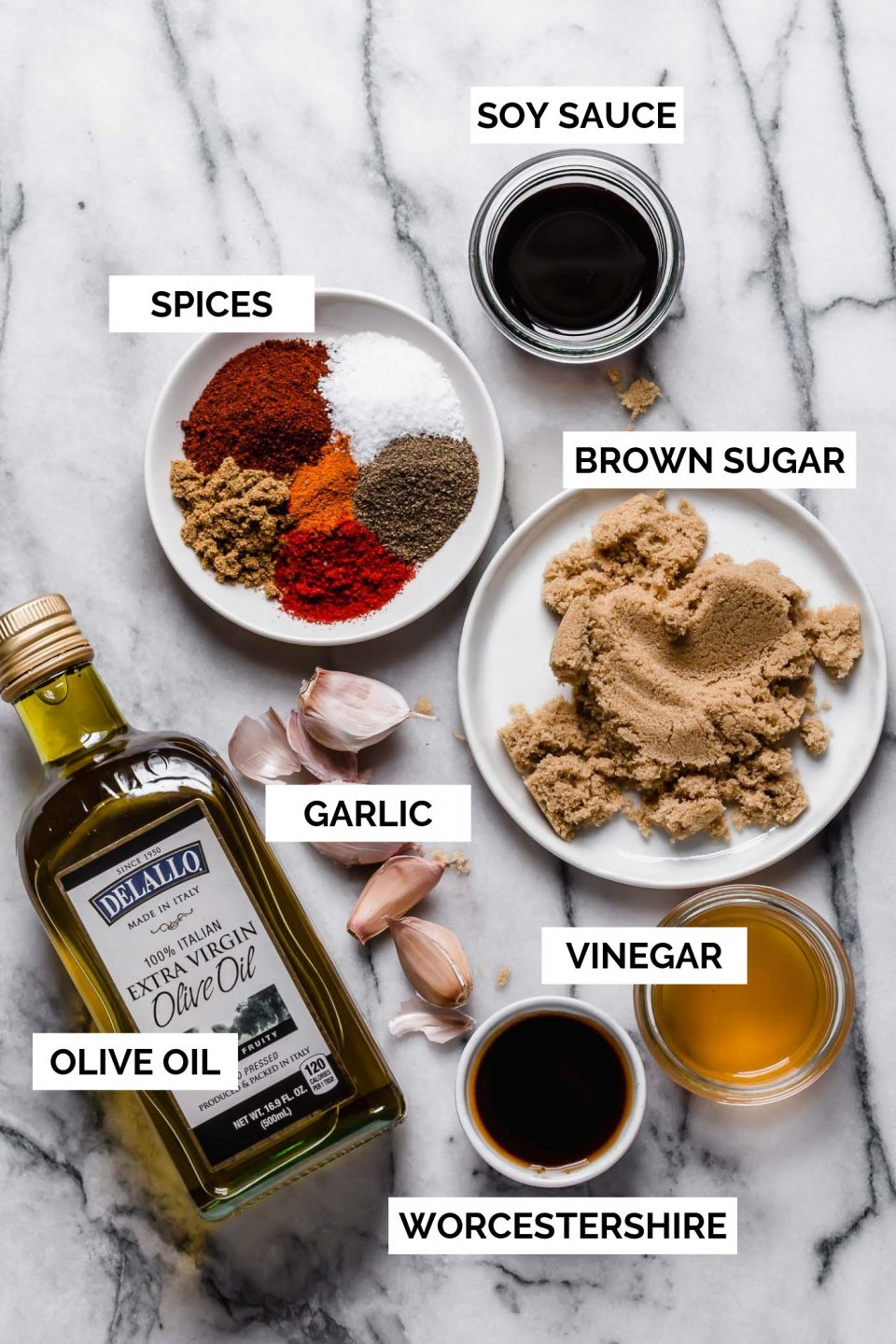 A flat-lay image with text overlay of each of the pantry ingredients (spices, soy sauce, brown sugar, garlic, vinegar, worcestershire, and olive oil) that make up the homemade grilling recipe
