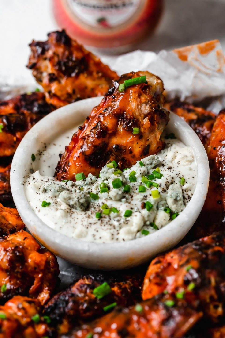 Grilled chicken wing shown being dunked in bleu cheese dipping sauce.