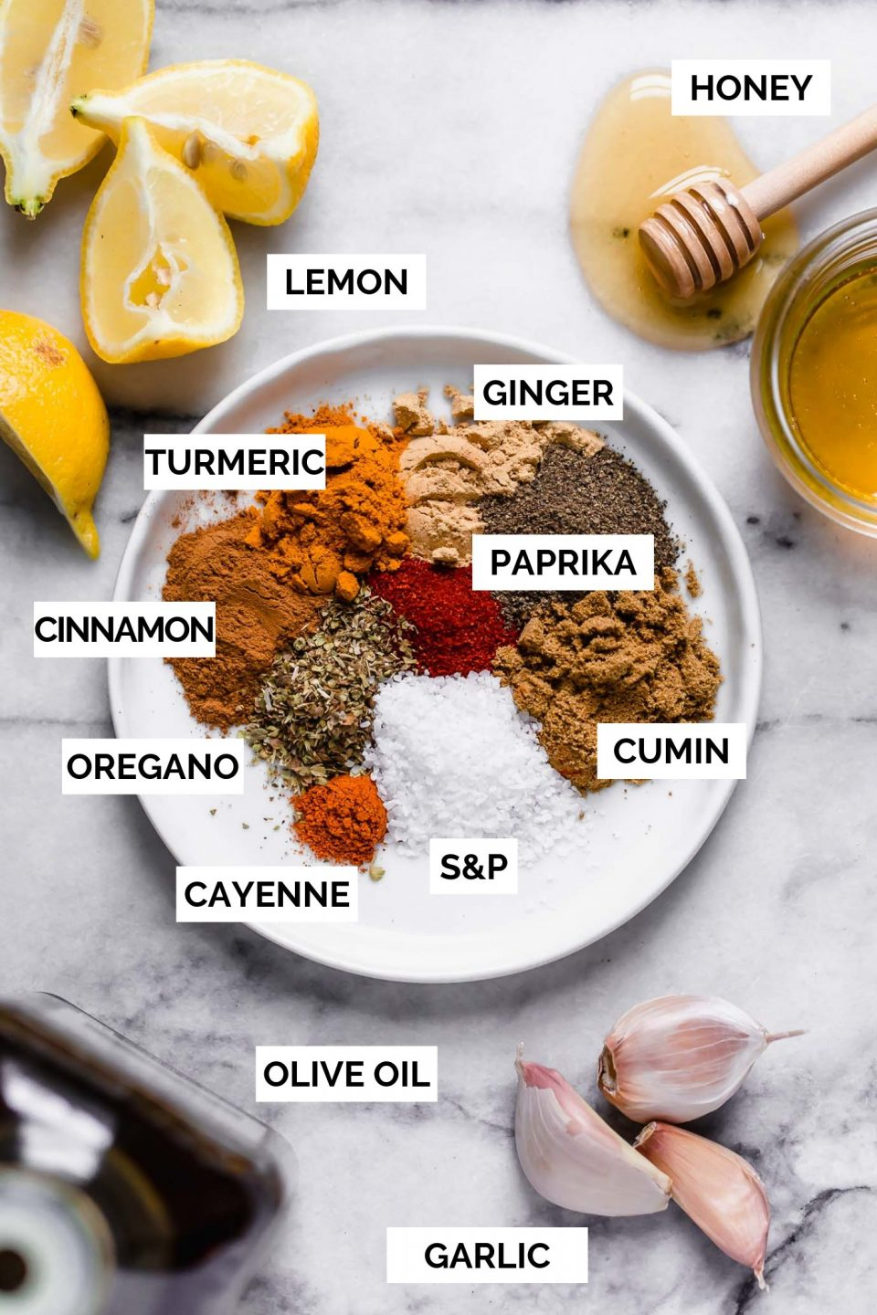 Shawarma ingredients (honey, lemon olive oil, and garlic) surrounding a white plate full of shawarma spices