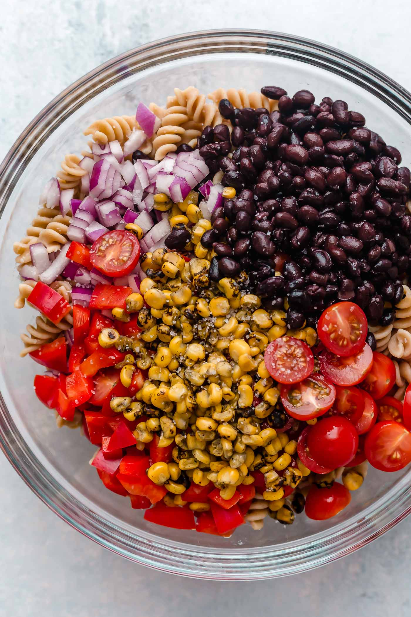 vegan southwest pasta salad recipe ingredients layered in a clear mixing bowl