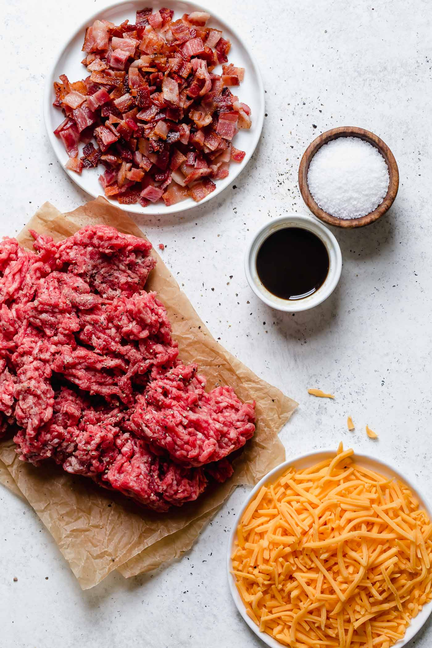 bacon cheddar stuffed burger ingredients (hamburger, bacon, cheddar cheese, worcestershire sauce, salt) arranged on a white backdrop.