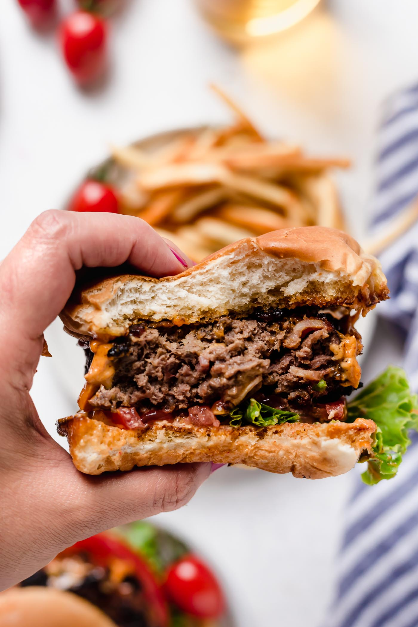 a woman's hand holding up stuffed bacon cheddar burger after a few bites have been taken out of it.