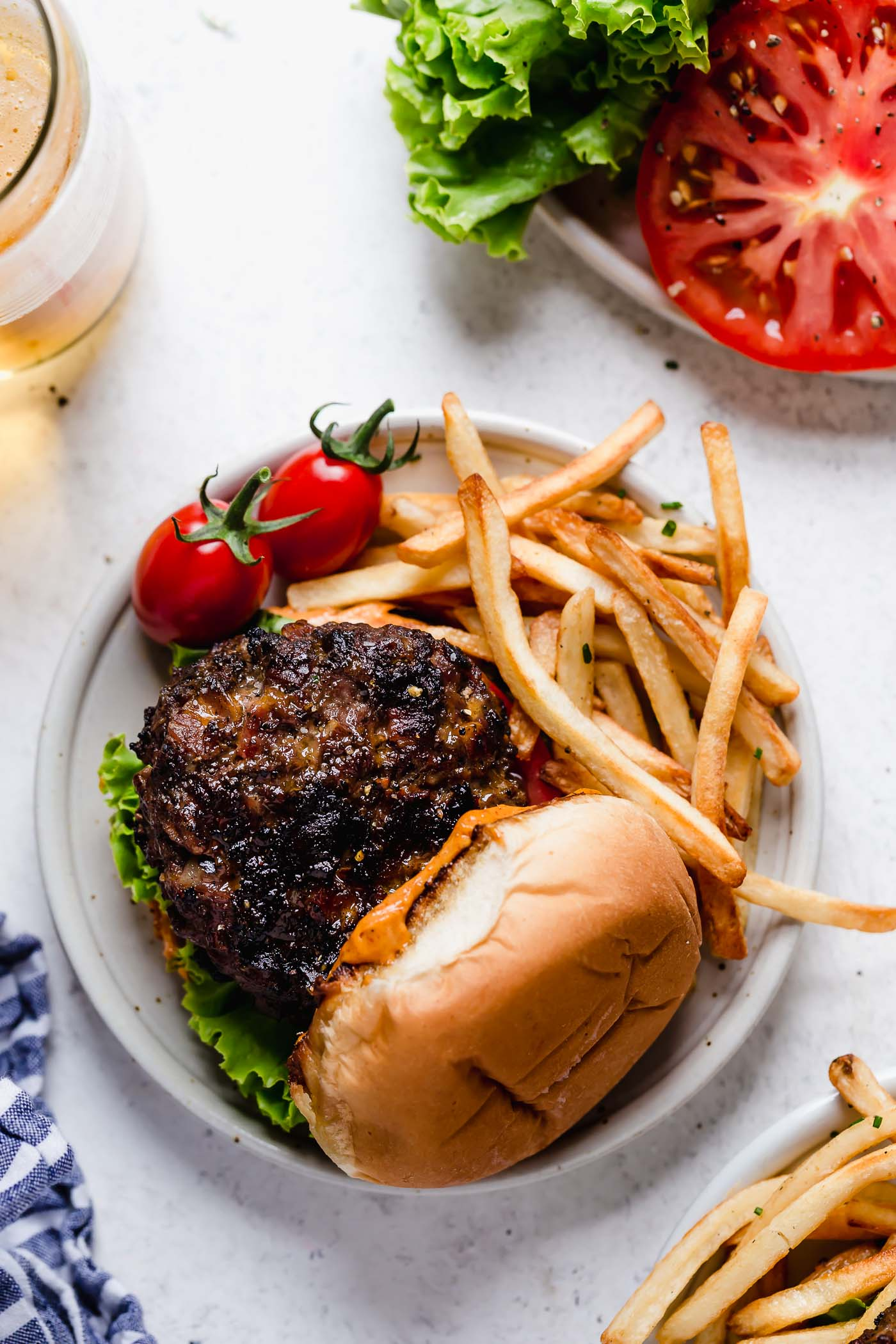 bacon cheddar stuffed burger served on a bun with french fries next to another plated burger, plated burger toppings & a ice cold beer.