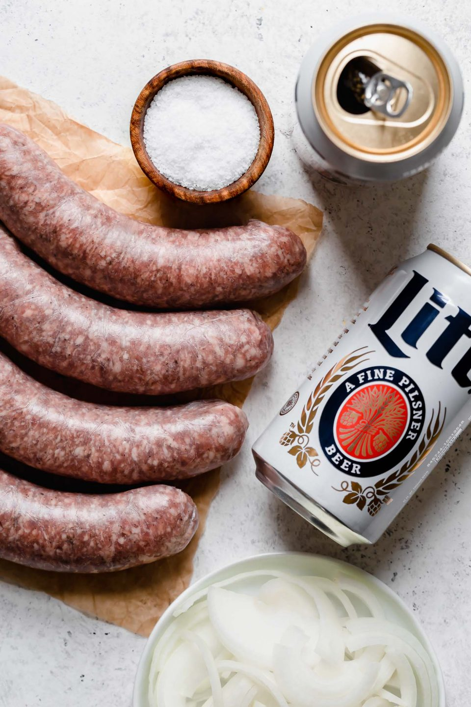 Beer brats ingredients arranged on a white surface - raw bratwurst sausage on a small piece of parchment paper, next to 2 cans of Miller Light & a white dish of thinly sliced onion.