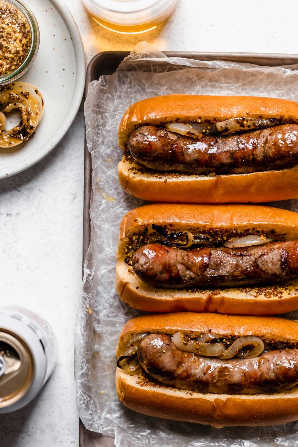 3 grilled beer brats on buns sit atop a parchment-paper lined metal baking sheet. The baking sheet is on a white surface, surrounded by a glass & can of beer, & a small plate with grilled onions.
