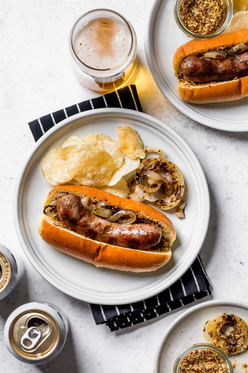Grilled Beer Brat on a brioche bun, sitting on a small white plate with potato chips & grilled onions. The plate is on a black & white striped napkin atop a white surface. Surrounding the plate is a glass of beer, cans of Miller Light beer, a small ramekin of whole grain mustard, & a second plate of beer boiled brats.