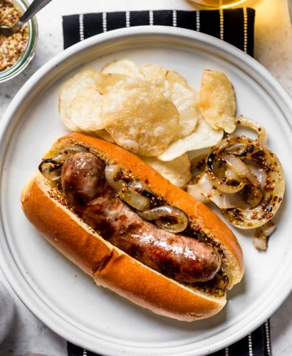 Grilled Beer Brat on a brioche bun, sitting on a small white plate with potato chips & grilled onions. The plate is on a black & white striped napkin atop a white surface. Surrounding the plate is a glass of beer, cans of Miller Light beer, & a small ramekin of whole grain mustard.