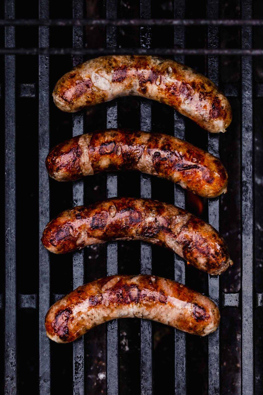 4 bratwurst sausage grilling on cast iron grill grates.