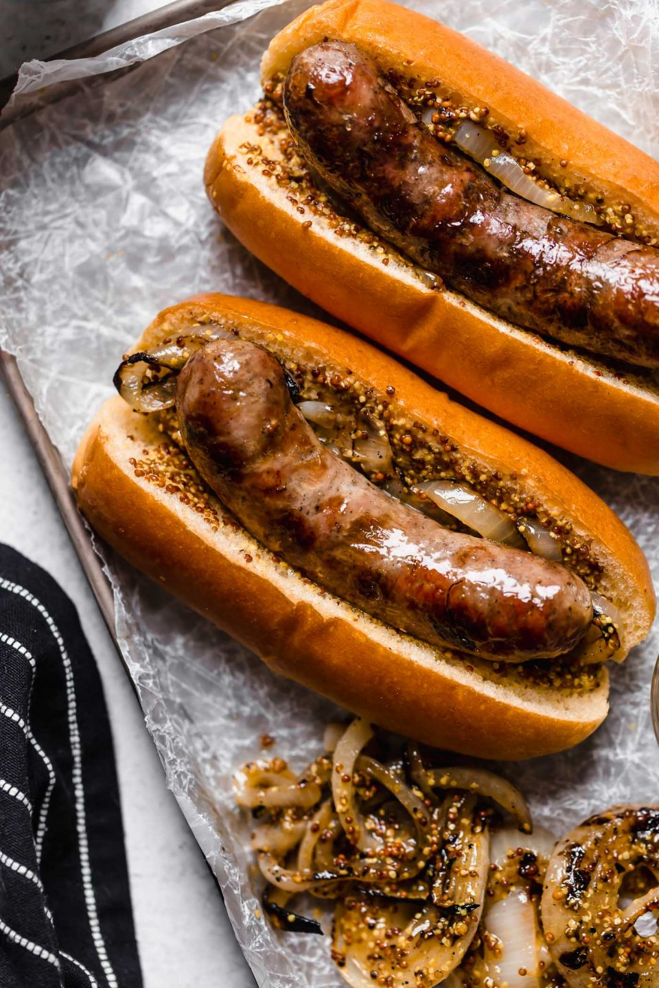 2 beer brats in brioche buns with mustard & grilled onions. The brats sit atop a piece of while parchment paper on a small metal baking sheet. The baking sheet sits next to a black & white striped napkin on a white surface.