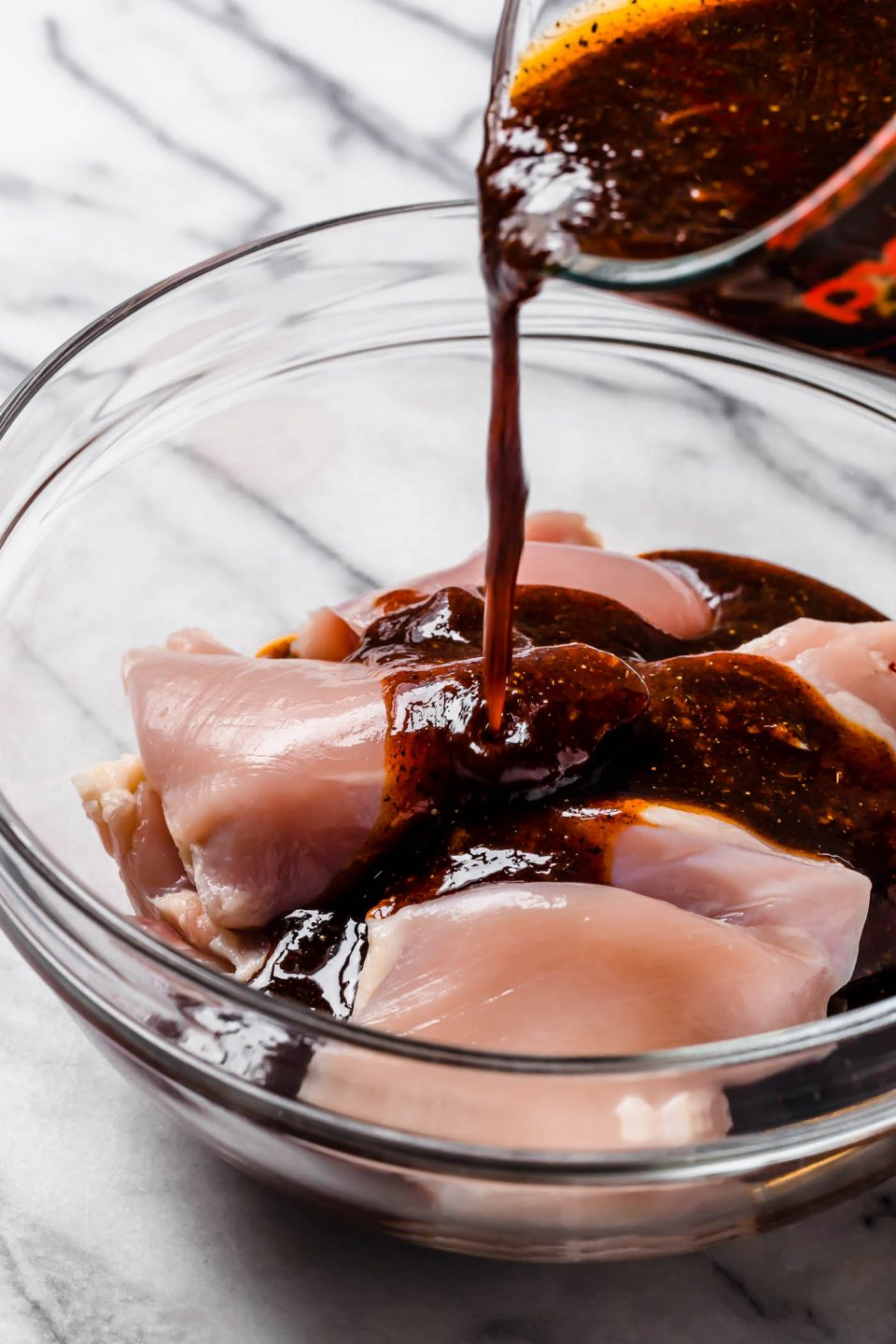 All purpose marinade is poured into a clear glass bowl of raw chicken thighs to marinate