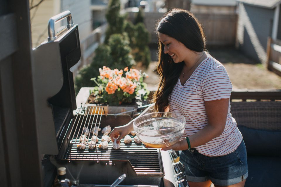 A smiling woman standing next to a grill with a bowl of brined chicken wings in one hand & placing the brined wings on the hot grill grates with the other hand.