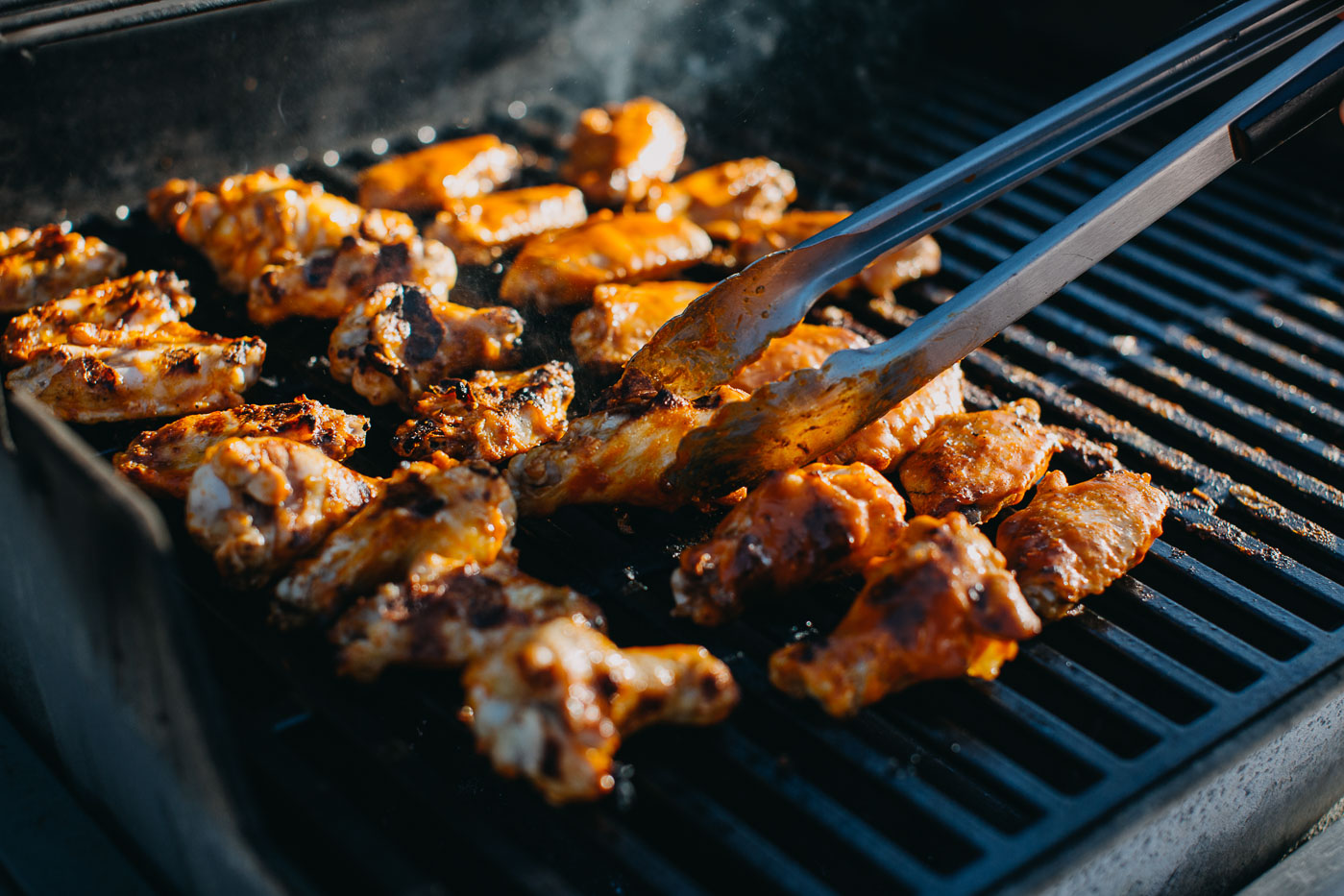 A few dozen chicken wings cooking on a grill grate. Grilling tongs reach into the frame of the image, turning one of the chicken wings.