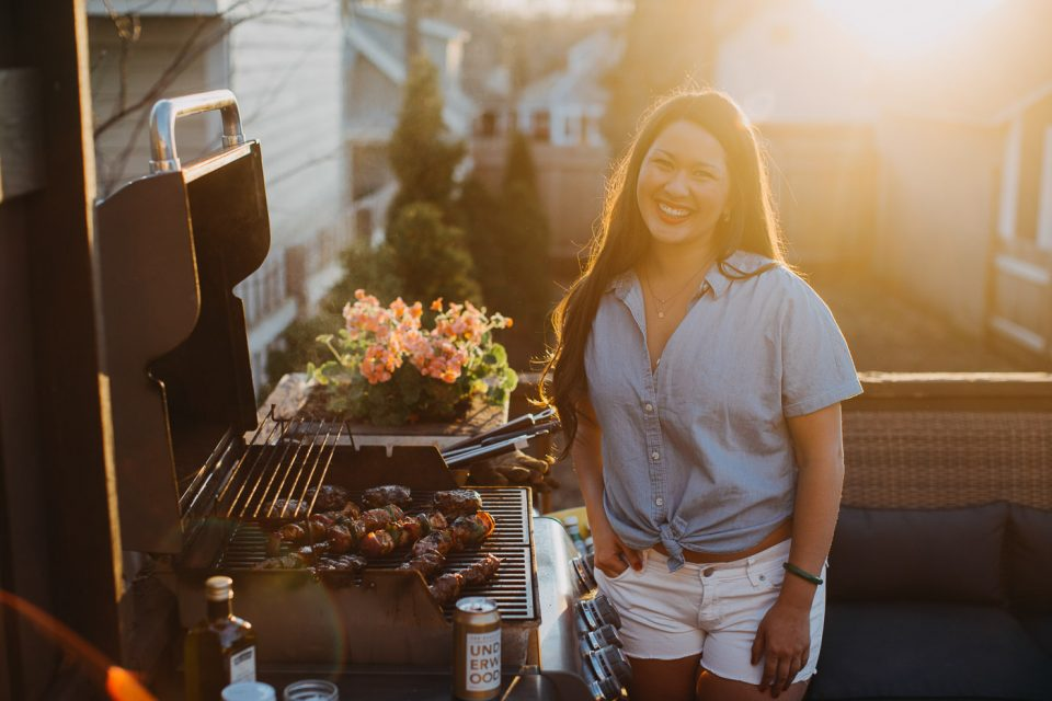 Jess of Plays Well with Butter standing next to her gas grill while grilling kebabs