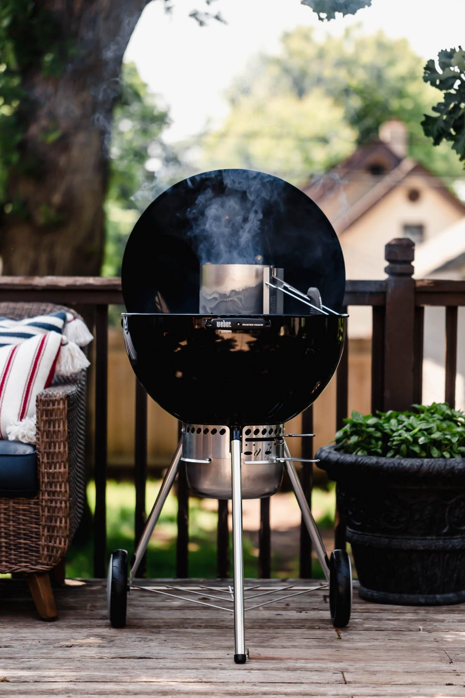 A 22-inch original weber grill sitting on a deck open to show a charcoal chimney with smoke coming out of it