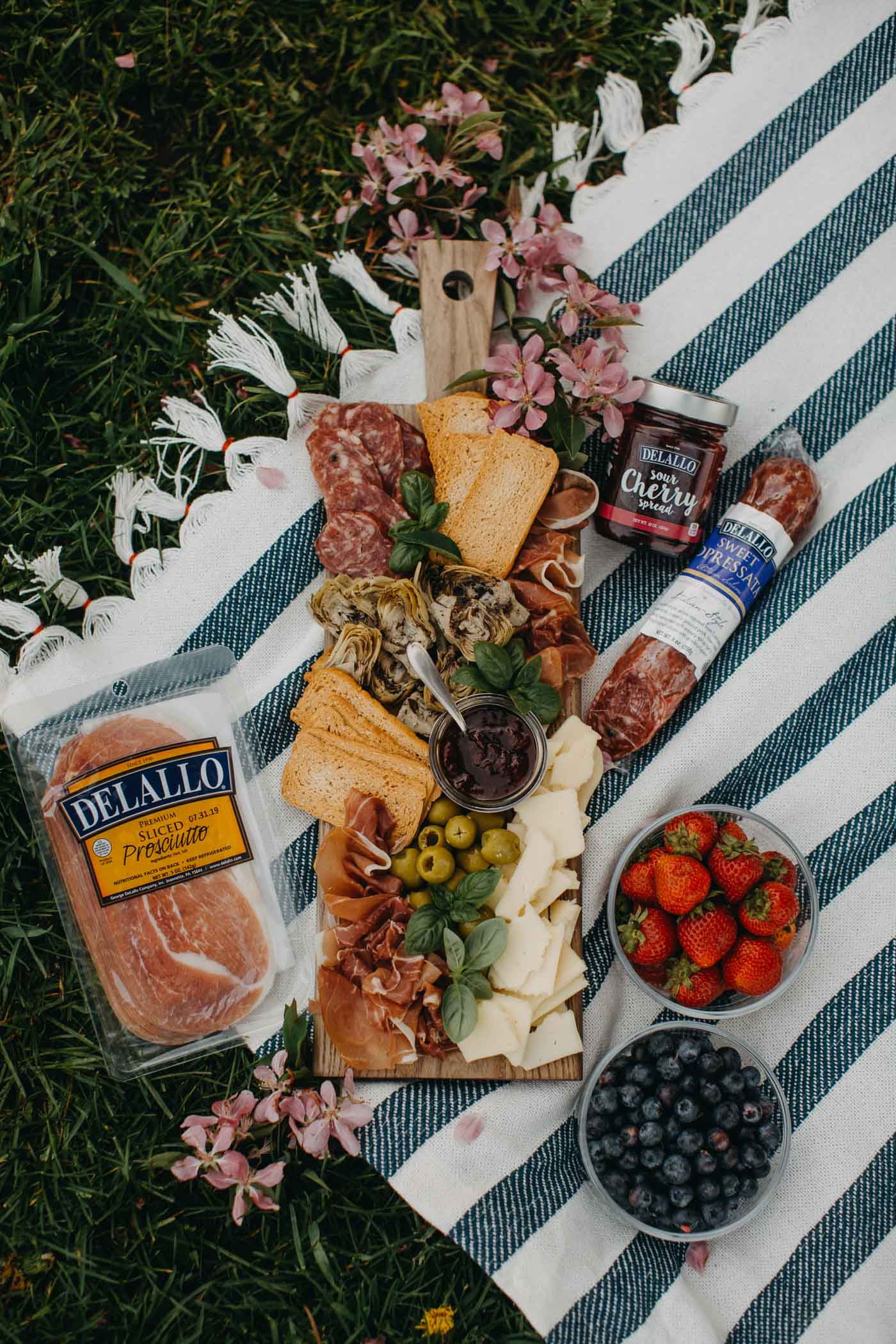 overhead view of summer charcuterie board on striped blue picnic blanket. board contains cheese, meats, olive, artichoke hearts, & fresh herbs.