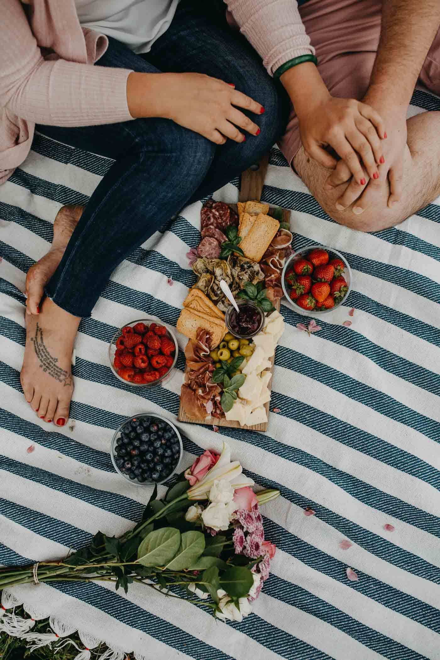 overhead view of a couple seated on a blue striped picnic blanket on the grass next to a lake with a summer picnic charcuterie board for 2, along with fresh flowers & a picnic basket.