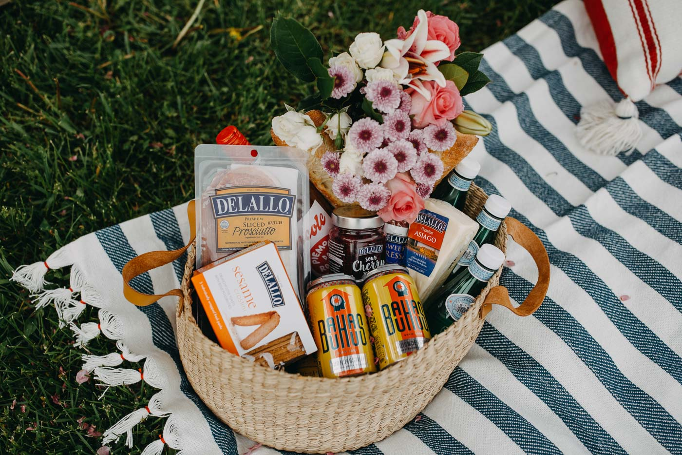 view inside summer picnic basket, which is filled with fresh flowers, wine, beer, & charcuterie board ingredients.
