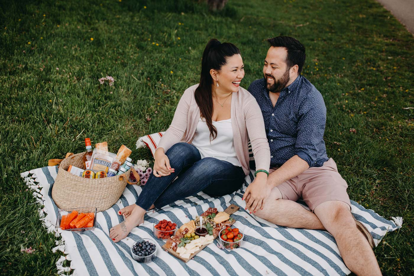 a couple seated on a blue striped picnic blanket on the grass next to a lake with a summer picnic charcuterie board for 2.