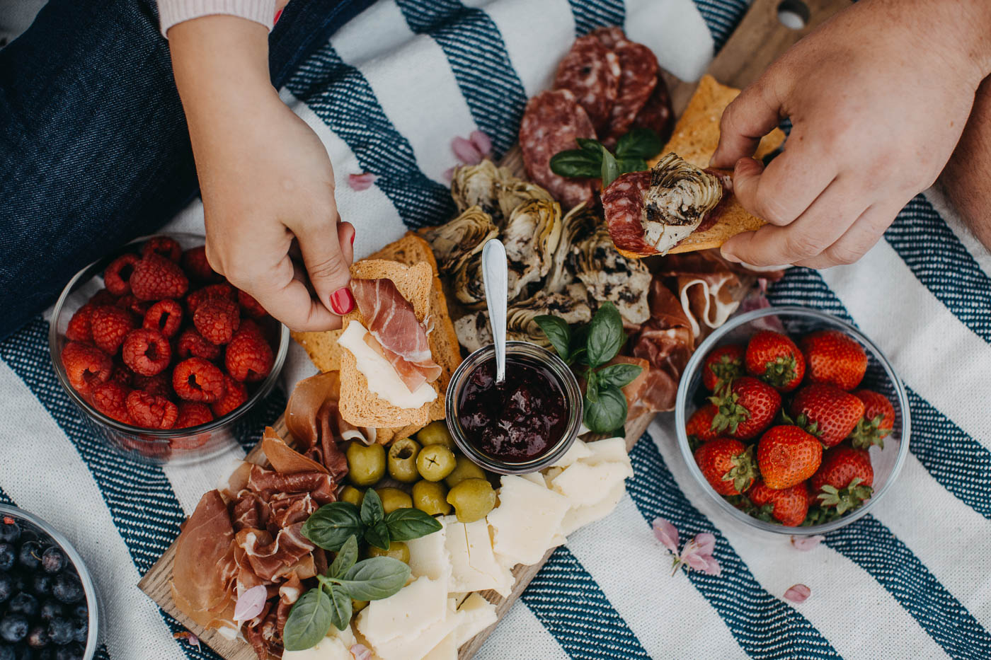 overhead view of a couple seated on a blue striped picnic blanket on the grass next to a lake with a summer picnic charcuterie board for 2. his & her hands are reaching into the board to build bites of charcuterie on crostini crackers.