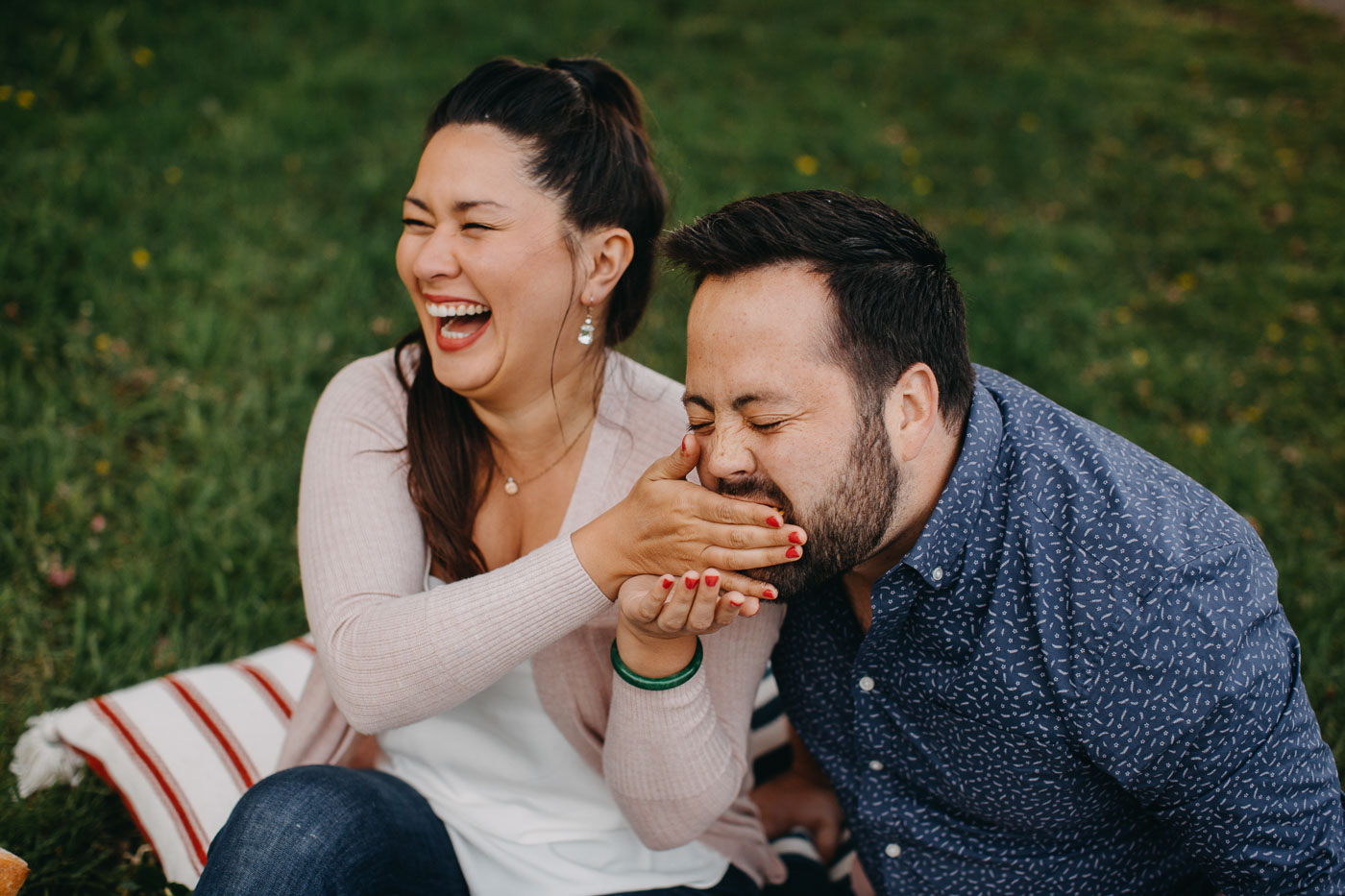 a couple seated on a blue striped picnic blanket on the grass next to a lake with a summer picnic charcuterie board for 2. she is feeding him a bite of charcuterie & they are both laughing.