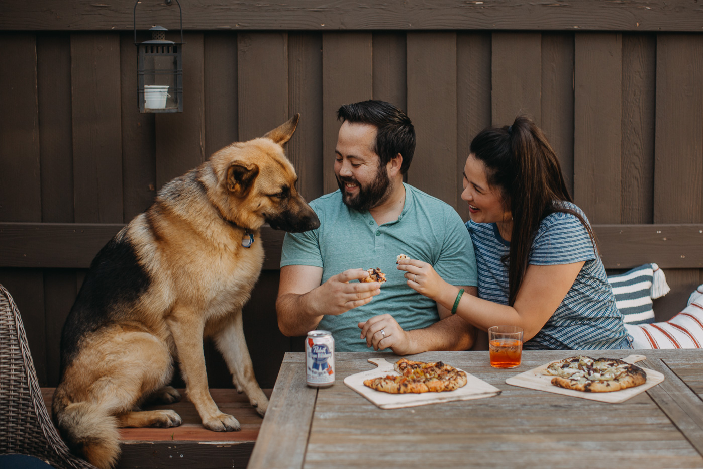 man & woman sitting at patio table enjoying homemade pizzas & drinks for pizza night with their dog.