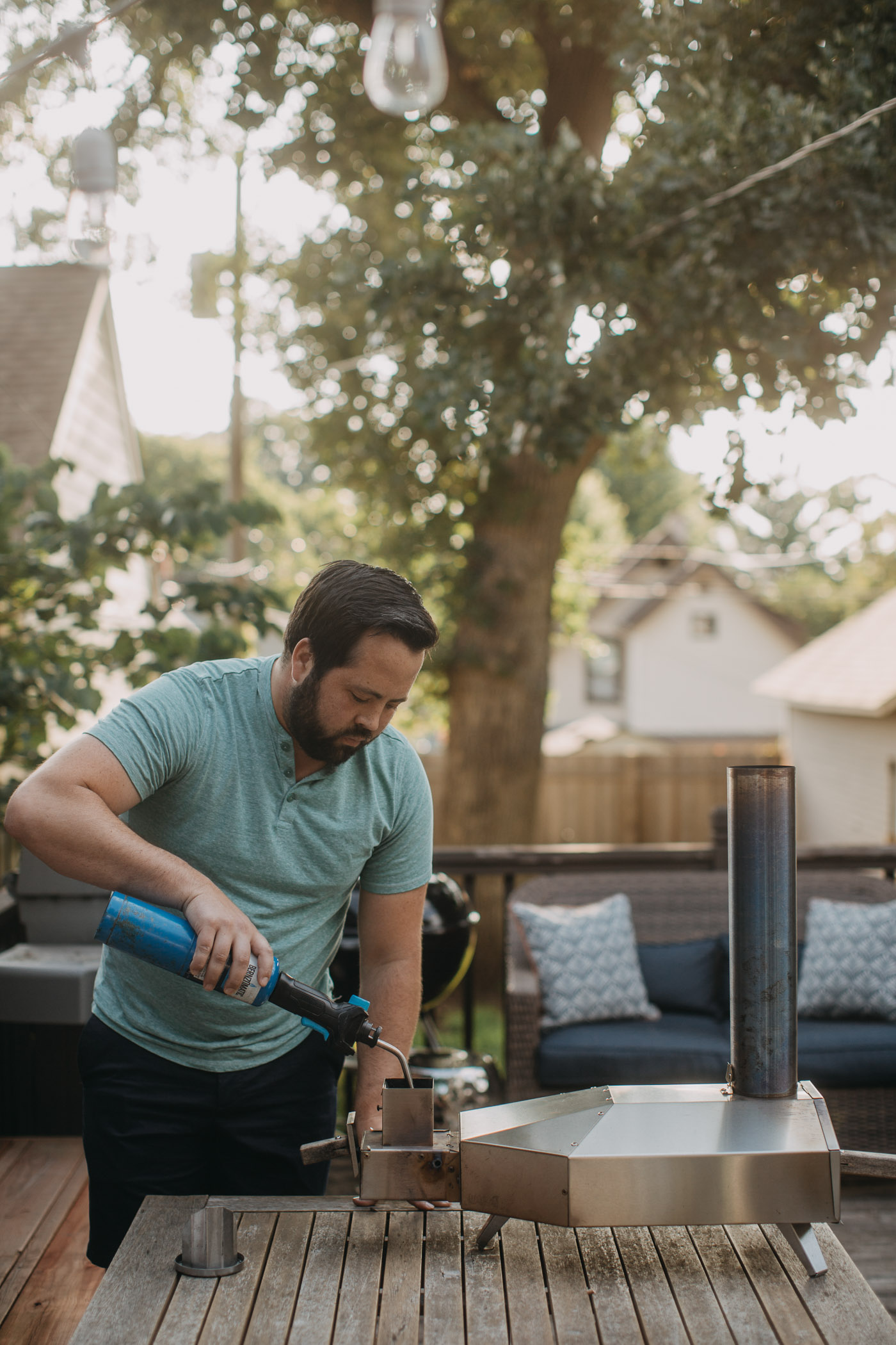 Bearded man in green shirt lighting an Ooni 3 outdoor pizza oven with propane torch.
