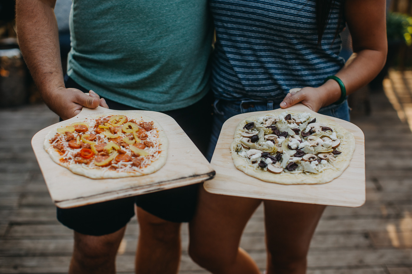 man and woman holding up pizza night homemade pizzas on 2 pizza peels.