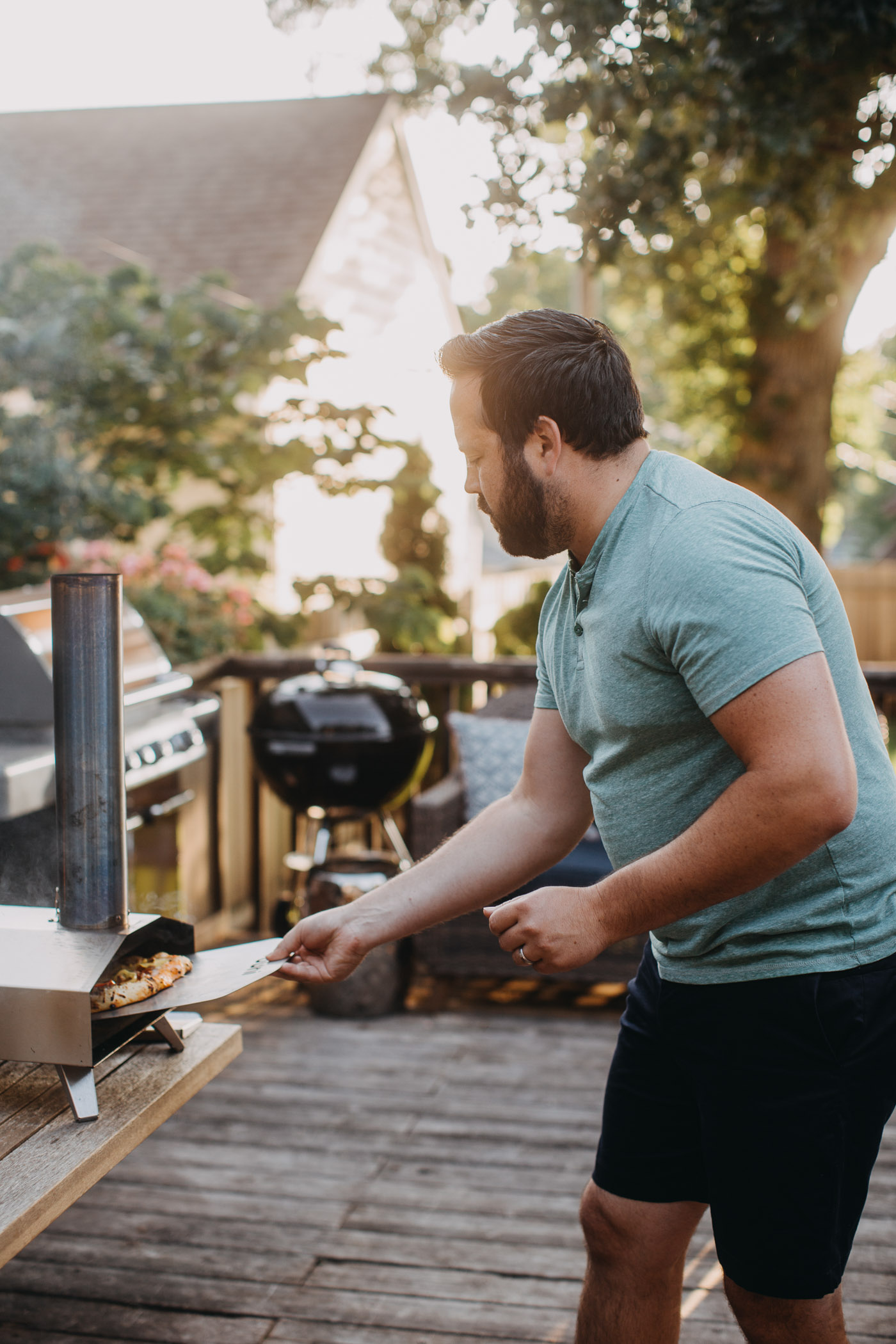 Bearded man in green shirt transferring homemade pizza from a pizza peel to an Ooni pizza oven (model: Ooni 3)