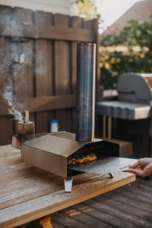 hand transferring homemade pizza from a pizza peel to an Ooni pizza oven (model: Ooni 3)