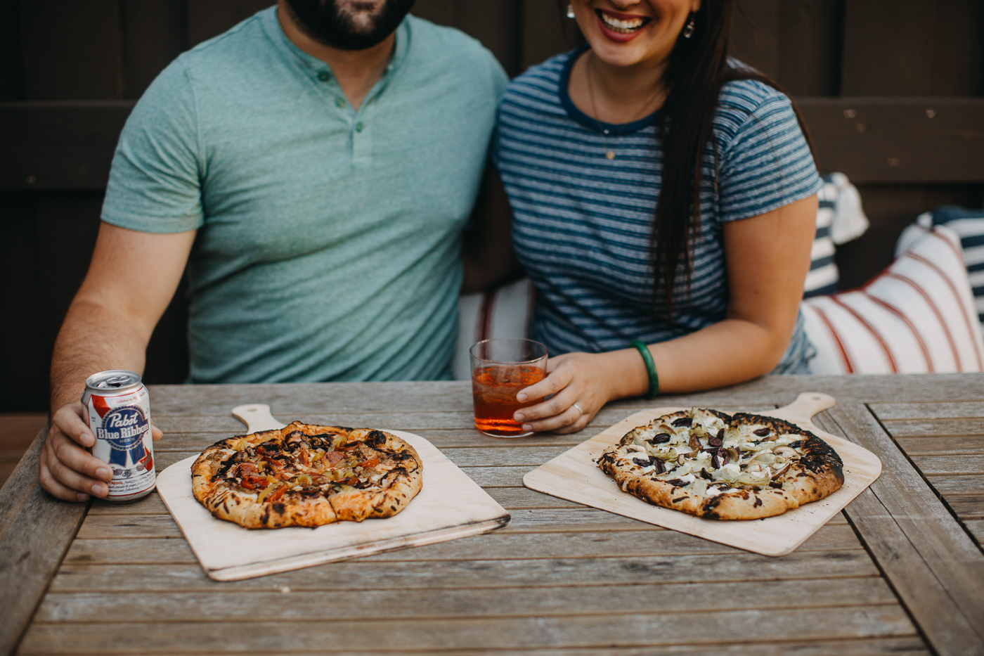 man & woman sitting at patio table enjoying homemade pizzas & drinks for pizza night.