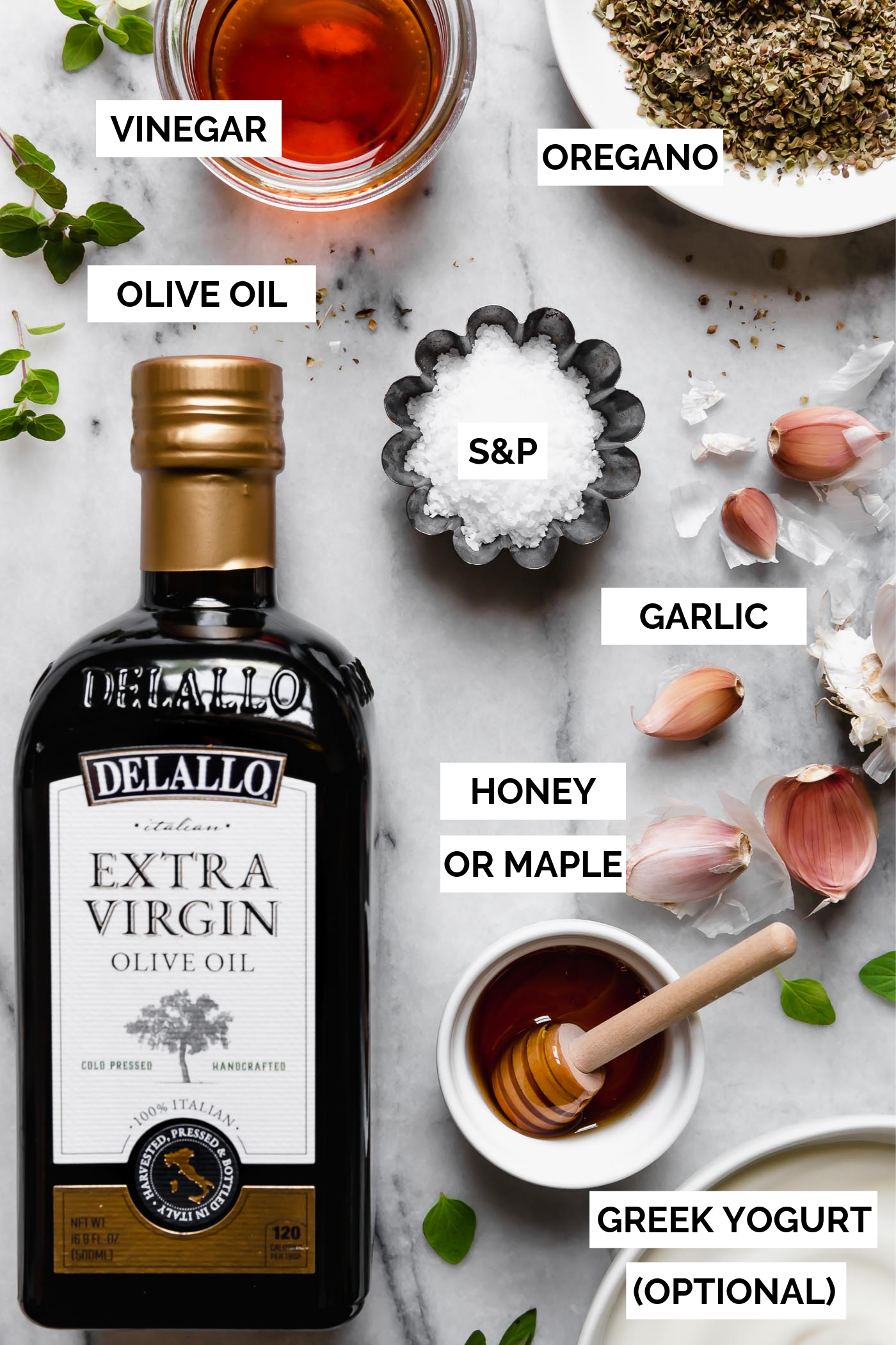 Easy Greek Dressing ingredients arranged on white marble background with text overlay stating each ingredient