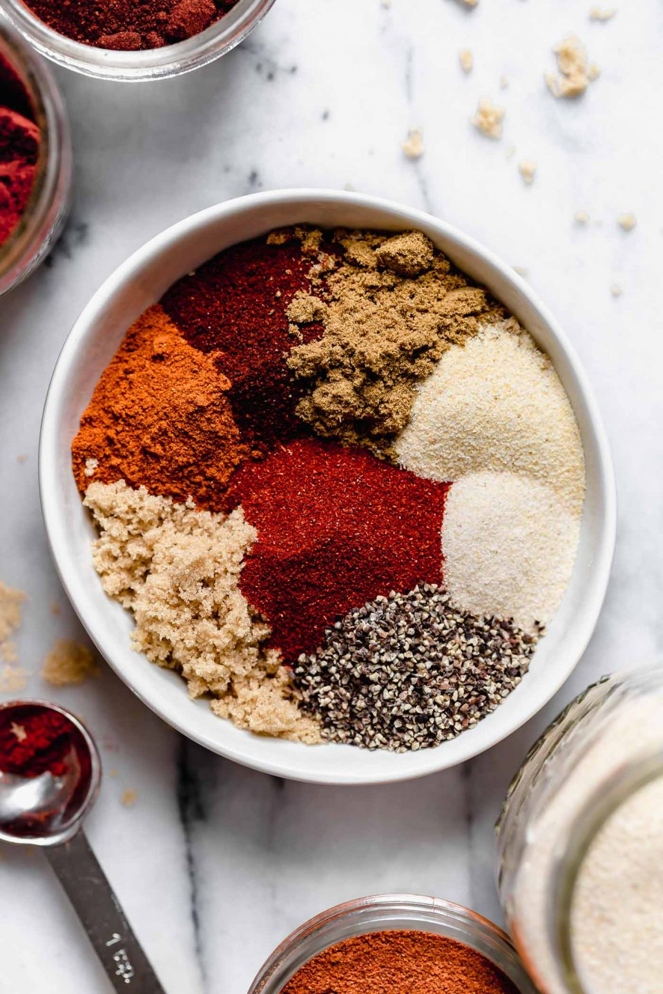 Ingredients for dry rub for baby back ribs shown in a small white bowl. Brown sugar, chili powder, cumin, onion powder, garlic powder, paprika, etc. The dry rub bowl is shown on a marble surface, next to a small measuring spoon & some larger jars of spices.