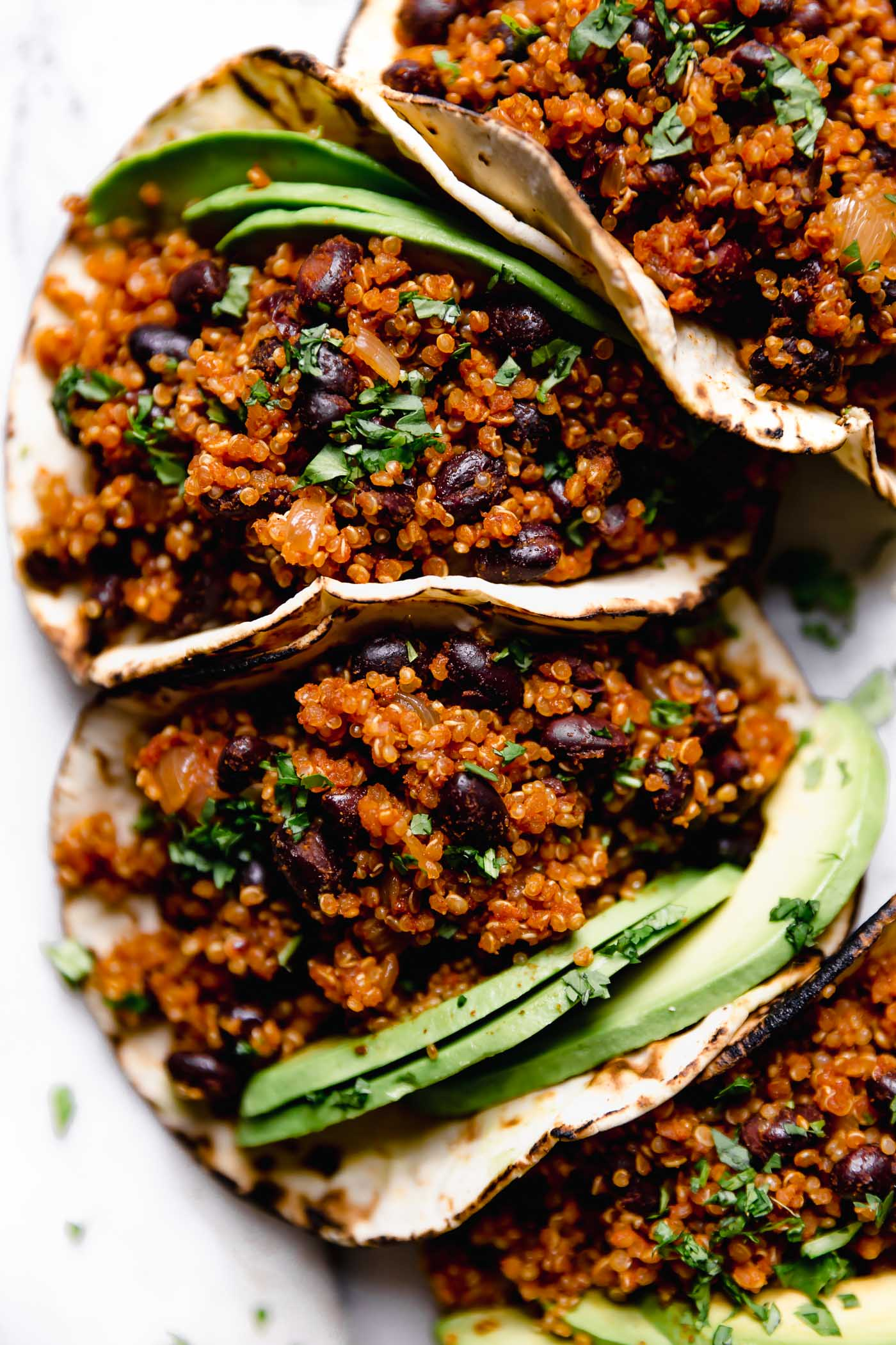 Quinoa & Black Bean Tacos arranged on a marble board, topped with chopped cilantro. There are a few lime wedges surrounding the tacos, along with a small blue bowl with the cilantro lime crema.
