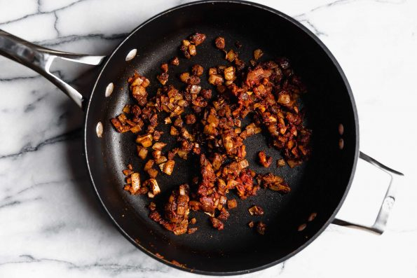 How to make Quinoa Taco Meat - Step 2: Aromatics coating softened onion in black skillet atop a white marble surface.