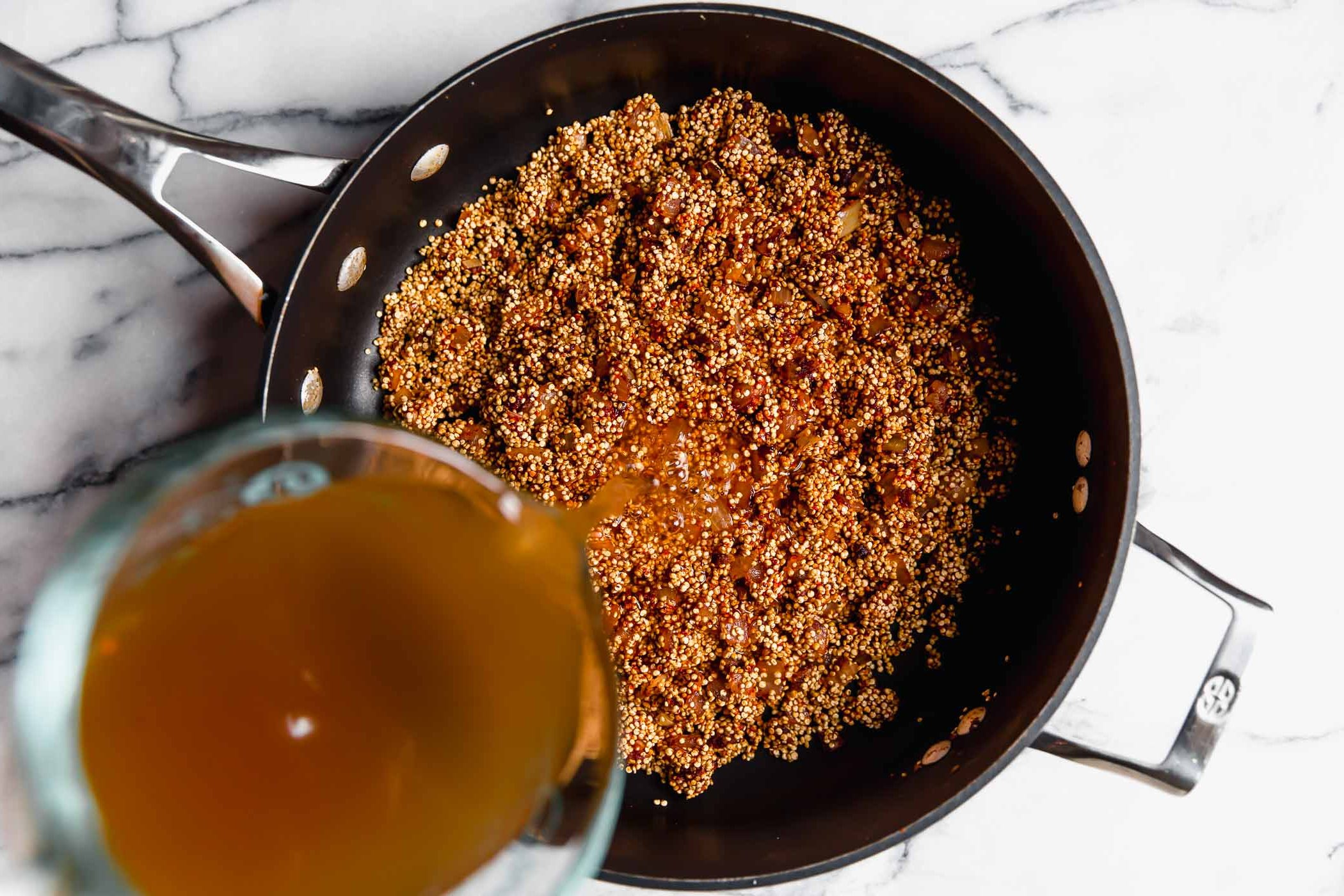 How to make Quinoa Taco Meat - Step 3: Adding vegetable stock to skillet with quinoa & aromatics.