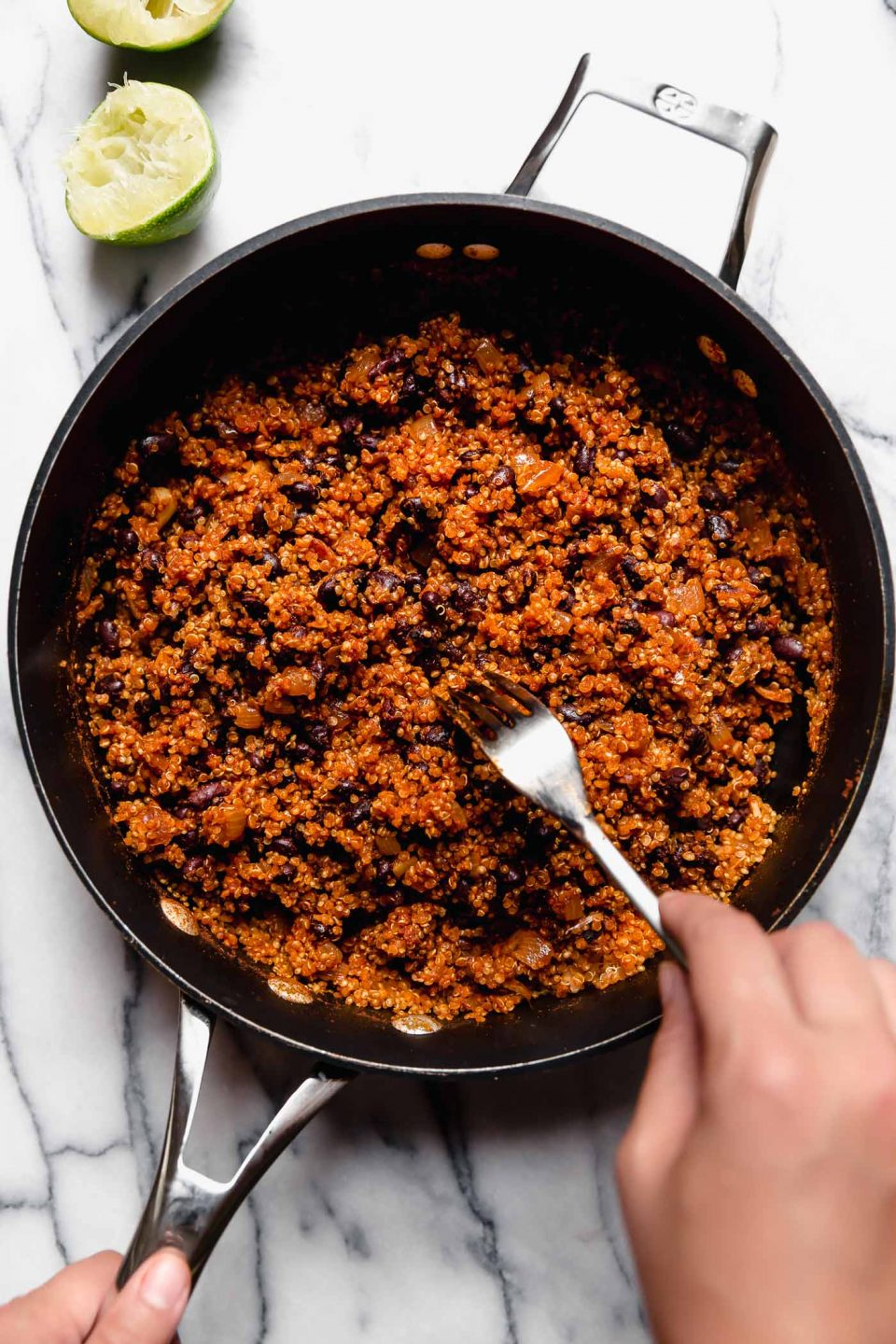 Hand reaching into the photo fluffing cooked quinoa & black bean taco filling (vegetarian taco meat) with a fork. The skillet is placed on a marble surface, with a few spent lime halves surrounding it.