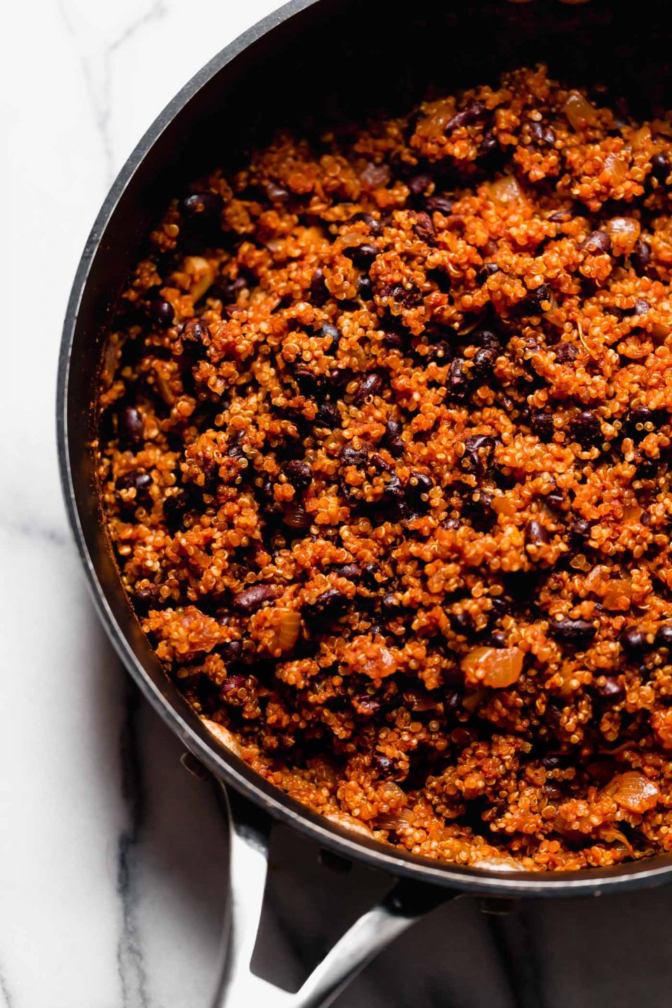 Cooked Quinoa Black Bean Taco filling (vegan taco meat) in black skillet on marble surface.