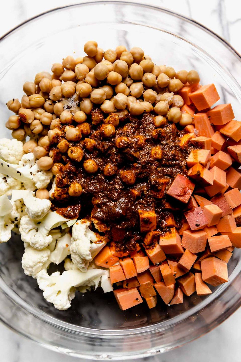 Cauliflower florets, diced sweet potatoes & chickpeas in a clear mixing bowl, topped with shawarma seasoning.