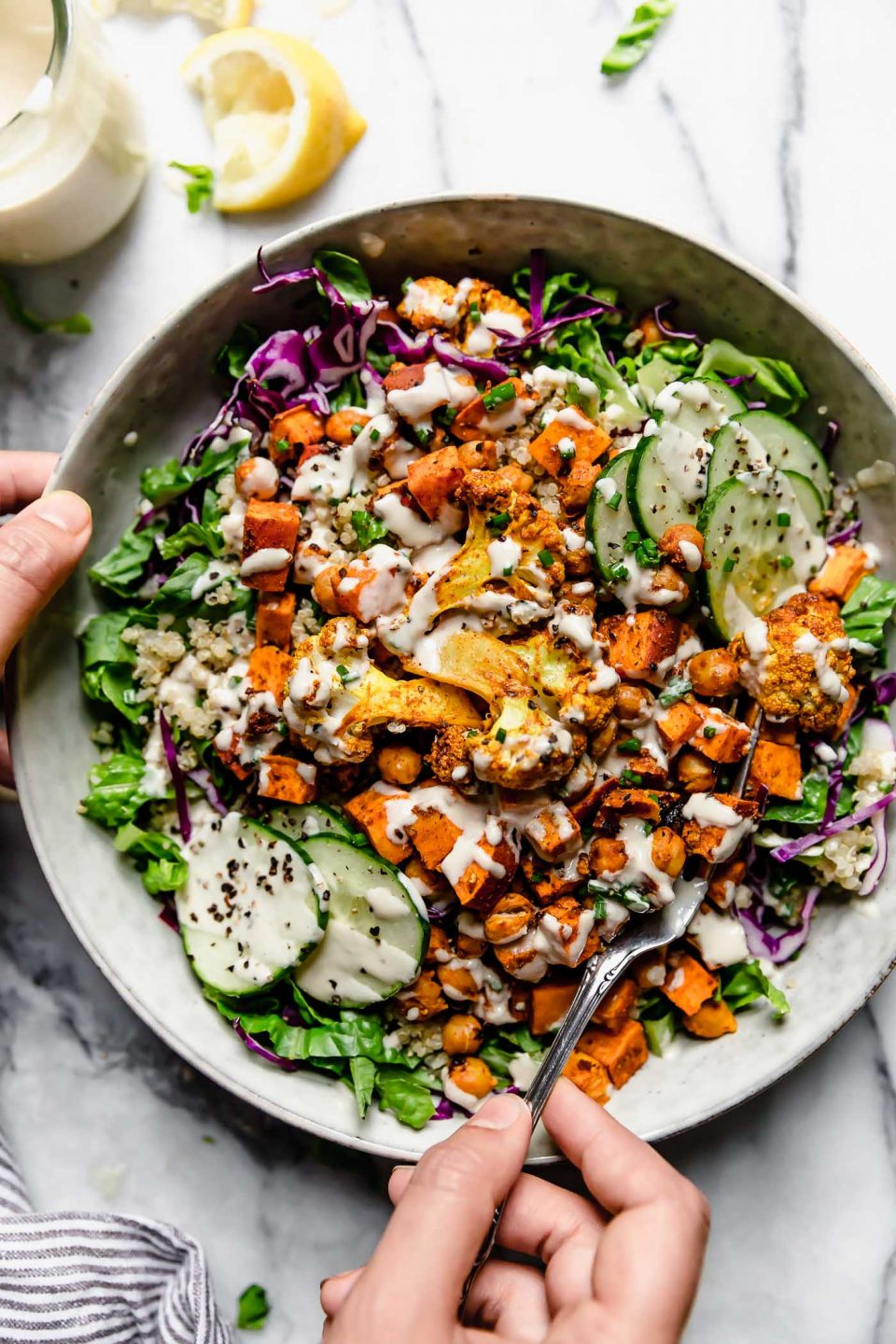 Roasted veggie & chickpea shawarma served in a bowl over greens & quinoa, drizzled with lemon tahini sauce. A woman's hands are reaching in from the left, holding a fork in the bowl.