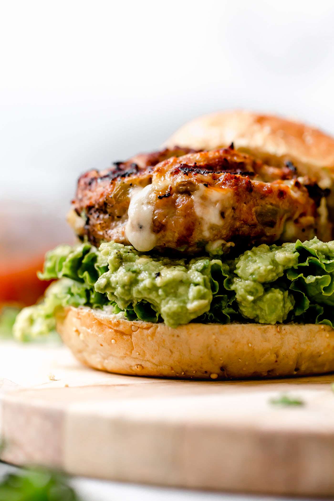 Zoomed in image of stuffed Southwest Turkey Burger place on a burger bun with lettuce & guacamole. Burger is sitting on a light wood board.