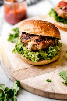 Stuffed Southwest Turkey Burger place on a burger bun with lettuce & guacamole. Burger is sitting on a light wood board, with a jar of salsa behind it.