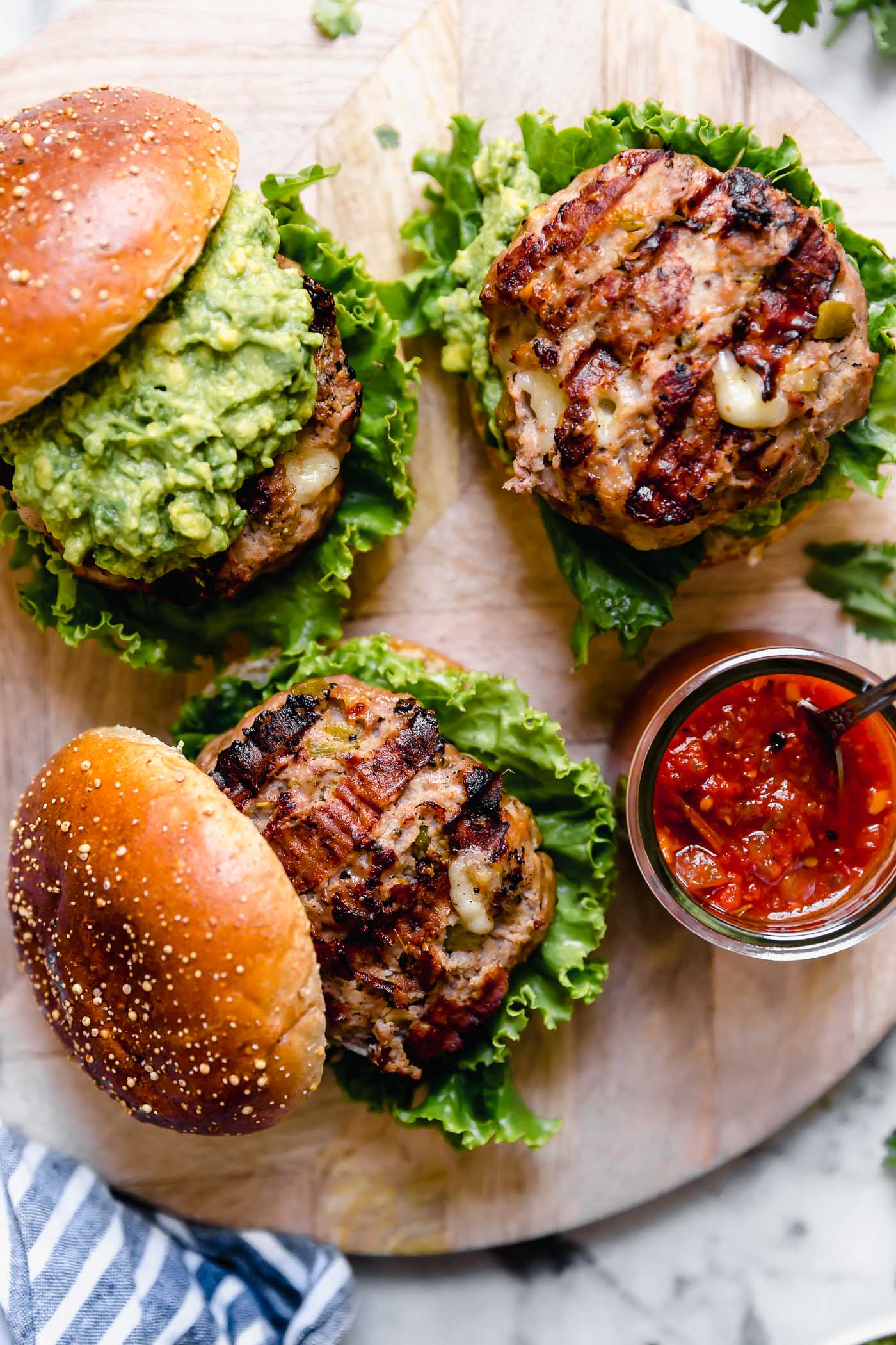 3 grilled stuffed turkey burger patties on a small white plate. The burgers have nice grill marks and are oozing with melted pepper jack cheese. Surrounding the plate are a jar of salsa, a brick of Tillamook pepper jack cheese, fresh cilantro, and a blue striped linen.